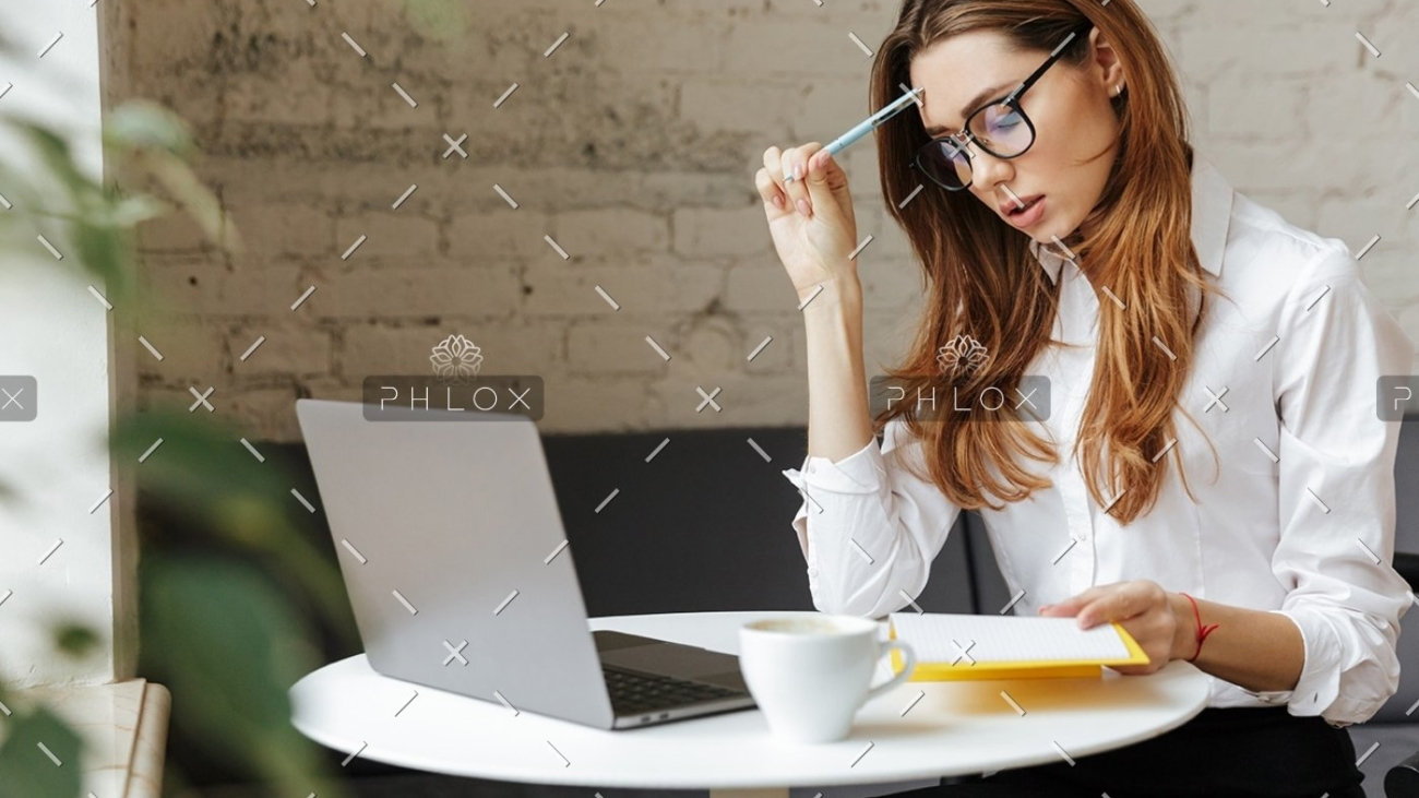 thoughtful-business-woman-indoors-using-laptop-P5HYUQX